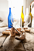 A corkscrew, corks, empty wine bottles and glasses