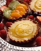 A lemon tartlet and a mixed fruit tartlet