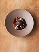 Chocolate ice cream bomb with pecan nuts and oranges on damson compote