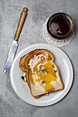Slices of toast with honey and daisies with a jar of honey next to it