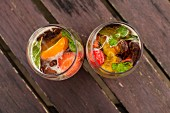 Two glasses of Pimms with fruit on a wooden table (seen from above)