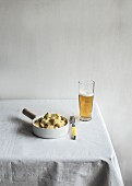A bowl of potato salad and a glass of beer on a table