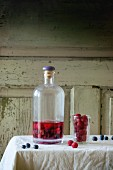 A bottle of homemade berry liqueur with strawberries and blueberries on a table with a white tablecloth