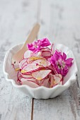 Radish carpaccio with hibiscus sea salt and edible flowers