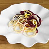 Vegetable spaghetti made from beetroot and yellow courgettes on a white plate