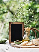 Ciabatta, olives, olive oil, grissini and a blackboard on a garden table