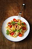Vegetables spaghetti made from kohlrabi with steamed cherry tomatoes and garlic
