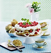 Raspberry cream cake, rolls and teacups