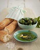 Olive oil, green olives and baguette