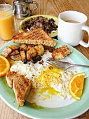 English breakfast with toast, fried egg, fried potatoes, coffee and juice