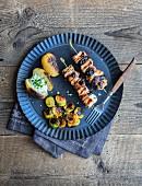 Schweinefleisch-Speck-Spiesse mit Trockenpflaumen, Rosenkohl und Baked Potato mit Sauerrahm