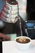 Water being poured into cup of coffee beans