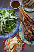 Grilled pork skewers, spring rolls, herbs and cucumber (Vietnam)