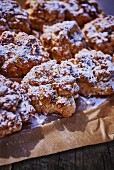 Biscotti with icing sugar on baking paper