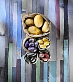Various types of potatoes in sacks on a colourful wooden surface (seen from above)