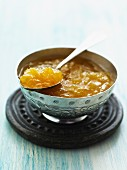 Apricot chutney in a metal bowl with a spoon
