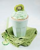 A kiwi cupcake in a ceramic cup