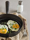 Fried eggs in a pan with fresh thyme