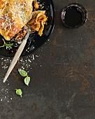 Eine Portion Lasagne und Rotweinglas