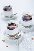 Trifle with quark, biscuit crumbs and cherries in glasses