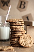 A stack of homemade oat biscuits with a glass of milk in the background