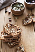 Wholemeal crackers with almonds, pumpkin seeds and dried cranberries on a wood surface