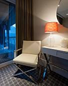 Sessel und Konsolentisch mit verchromten Stahrohrgestellen; brennende Tischleuchte und Abenddämmerung durch Fensterfront