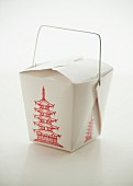 A takeaway box of oriental food on a white surface