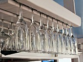 Champagne and wine glasses hanging upside down in a shelf in a restaurant
