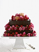 A two tier chocolate cake decorated with rosebuds