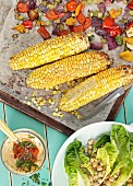 Oven-roasted vegetables and corn cobs with a salad and a dip