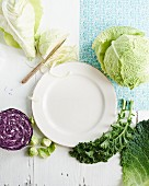 Various types of cabbages around a white plate