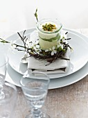 Mascarpone desert with kiwis and pistachio nuts decorated with twigs and flowers