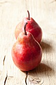 Two red pears on a wooden surface