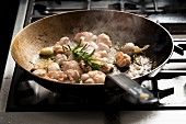 Fried veal sweetbreads with garlic and rosemary in a pan