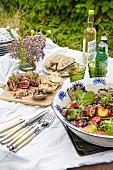 Sommerlicher Buffettisch im Freien mit Salat, Häppchen und Getränken