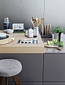 Kitchen utensils on counter with wooden worksurface
