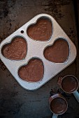 Chocolate cake mixture for heart-shaped cupcakes in a baking tray