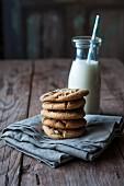 Gestapelte Chocolatechip Cookies auf Tuch vor Milchflasche