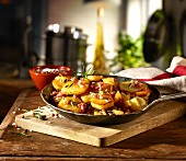 Fried potatoes with bacon and rosemary in a rustic pan