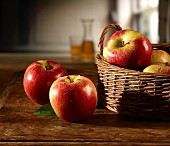 Red apples on a wooden table and in basket