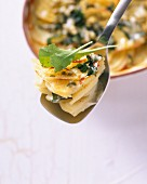 Potato and dandelion leaf gratin on a spoon above a baking dish
