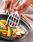 Kartoffeln, Bohnen und Kirschtomaten in der Pfanne braten