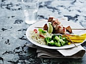Marinated pork skewers with tagliatelle, broccoli and mango