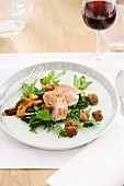 Chicken breast on a herb salad with croutons