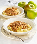 Two bowls of apple crumble with fresh apples next to them