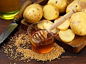 Ingredients for potato crisps (honey, mustard seeds and potatoes)