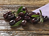 Kalamata olives with leaves on a wooden surface