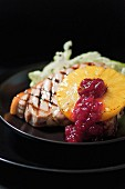 A grilled pork chop with grilled pineapple, lettuce and cranberry jam