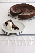 Chocolate tart, sliced, and a single slice with cream on a plate